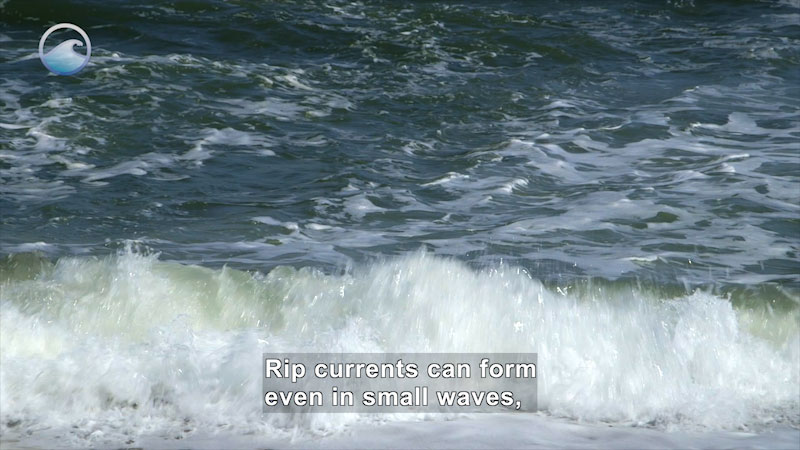 Close up of a wave crashing on shore. Caption: Rip currents can form even in small waves,