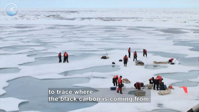 People in full-body orange and black clothing with gear standing on ice in pockets of water. Caption: to trace where the black carbon is coming from.