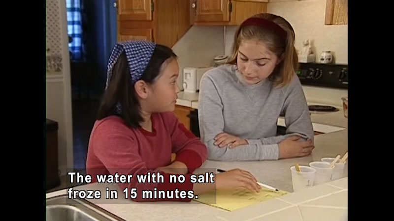 Two people at a kitchen counter. Three plastic cups containing liquid sit in front of them. Caption: The water with no salt froze in 15 minutes.