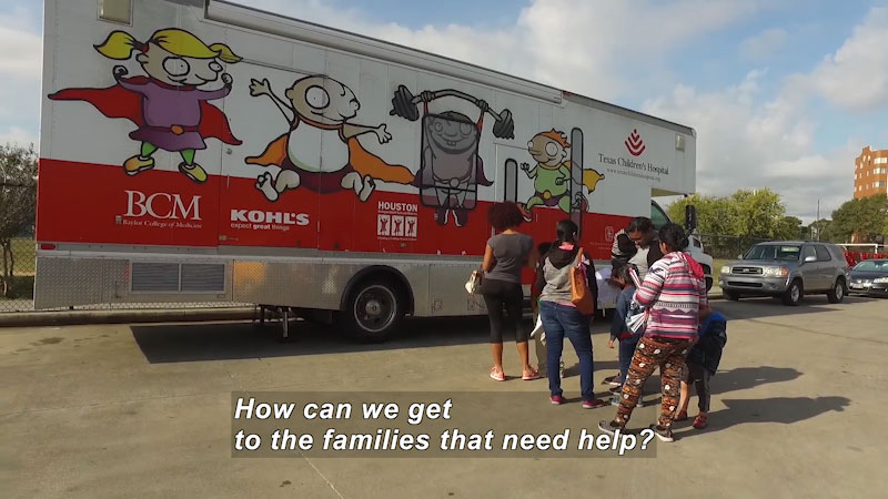 People lined up outside a mobile health clinic. Caption: How can we get to the families that need help?