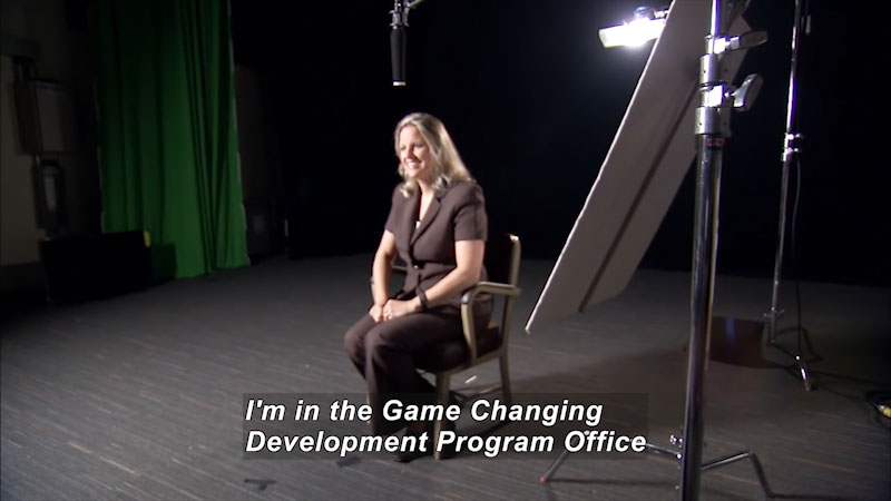 Woman speaking. Caption: I'm in the Game Changing Development Program Office