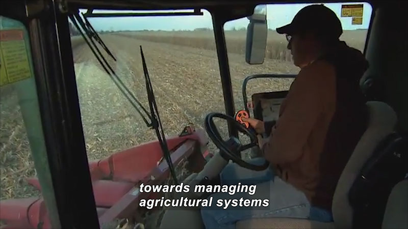 Person driving a large piece of industrial farm equipment. Caption: towards managing agricultural systems