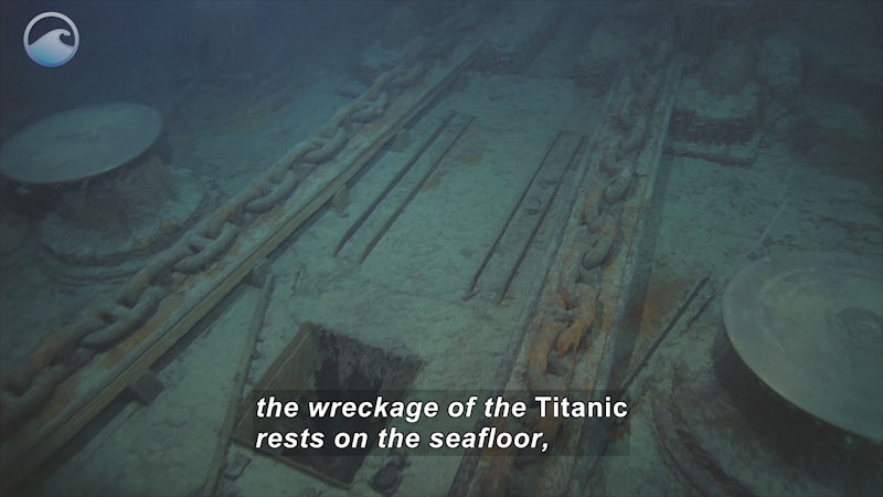 The deck of an underwater ship covered in debris and rusted metal. Caption: the wreckage of the Titanic rests on the seafloor,