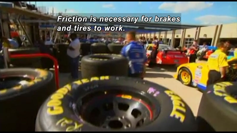 Pit crew station filled with tires at a racetrack. Caption: Friction is necessary for breaks and tires to work.