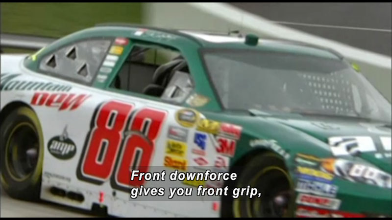 Race car on a track. Caption: Front downforce gives you front grip,