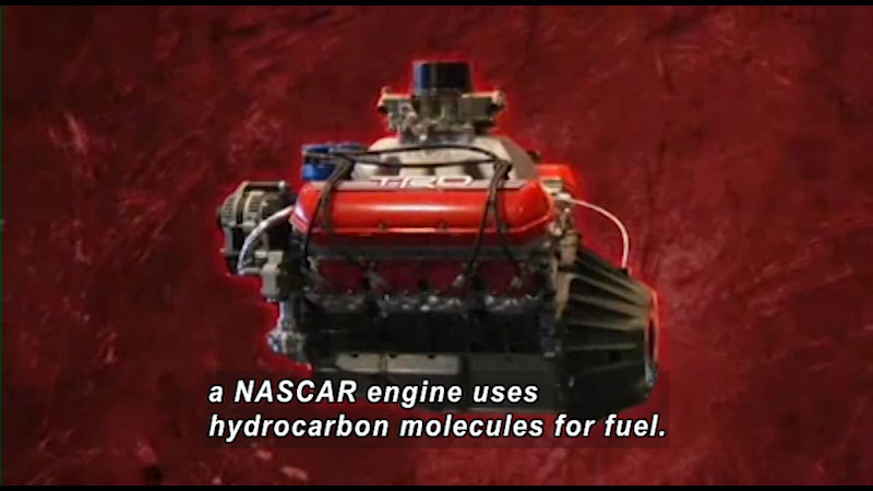 Side view of an engine. Caption: a NASCAR engine uses hydrocarbon molecules for fuel.