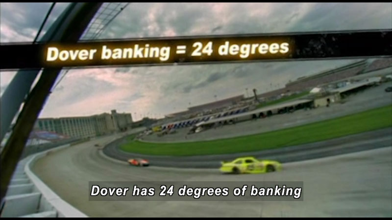 Two race cars barreling around a corner. Caption: Dover has 24 degrees of banking