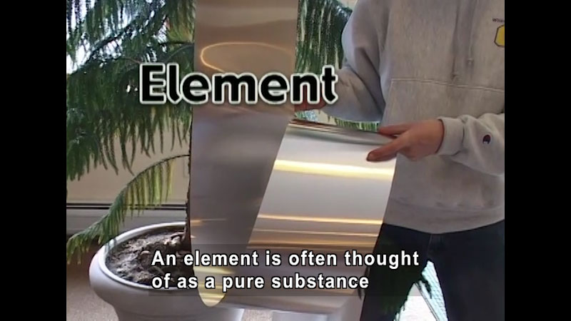 Person holding a sheet of a shiny metal. Caption: An element is often thought of as a pure substance
