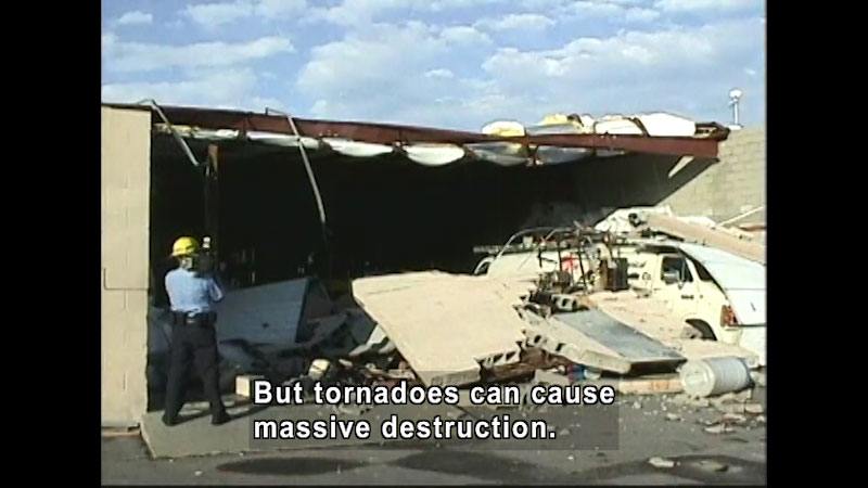 Partially collapsed building covering a vehicle in debris. A person wearing a hard hat films the destruction. Caption: But tornadoes can cause massive destruction.