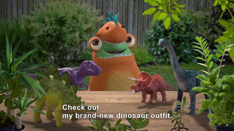 Cartoon character in a costume. On the table in front of it are toy dinosaurs. Caption: Check out my brand-new dinosaur outfit.