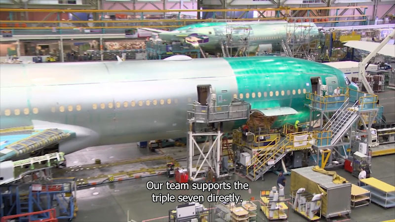 Large warehouse with airplanes in various stages of construction. Caption: Our team supports the triple seven directly.