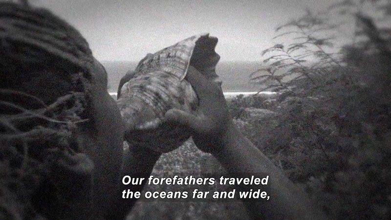 Person holding a shell to their mouth. Caption: Our forefathers traveled the oceans far and wide,