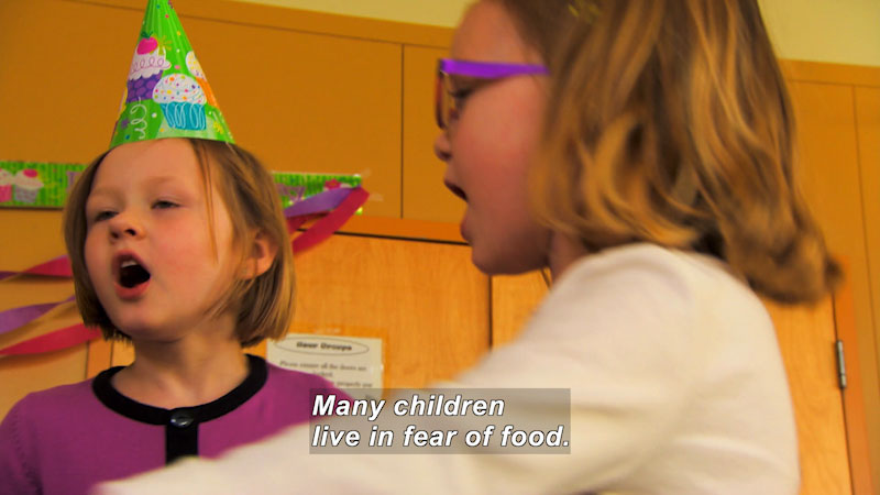 Children singing. Caption: Many children live in fear of food.