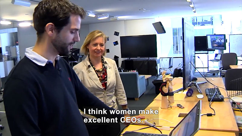 A man talks to a woman in an office setup. Caption: I think women make excellent C E Os.
