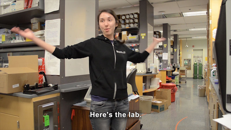 Alex Dainis stands in the aisle of her lab with her arms wide open. Caption: Here's the lab.