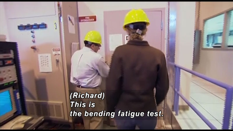 A man and woman have donned helmets and are about to enter a door. Caption: Richard, this is the bending fatigue test.
