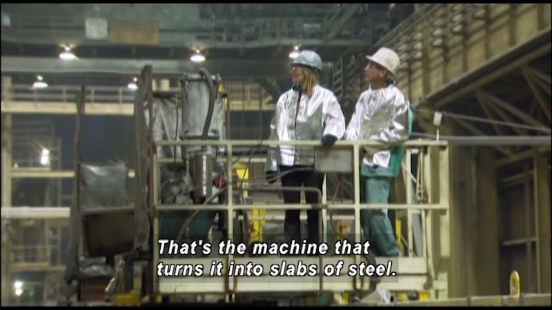 A man and woman have donned helmets and are on a x ladder. Caption: That's the machine that turns it into slabs of steel.