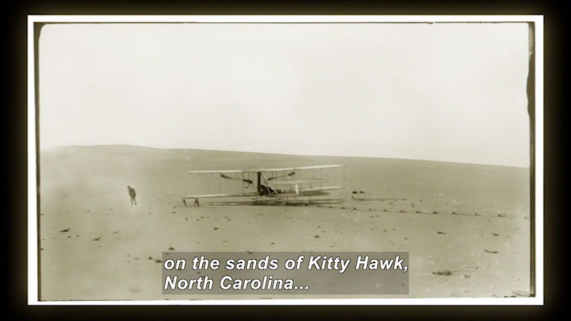 Oliver and Wilber Wright are testing their flight in the open sands. Caption: on the sands of Kitty Hawk, North Carolina.