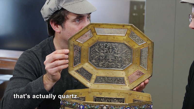 A man holds a transparent lid of a decorated container. Caption: That's actually quartz.