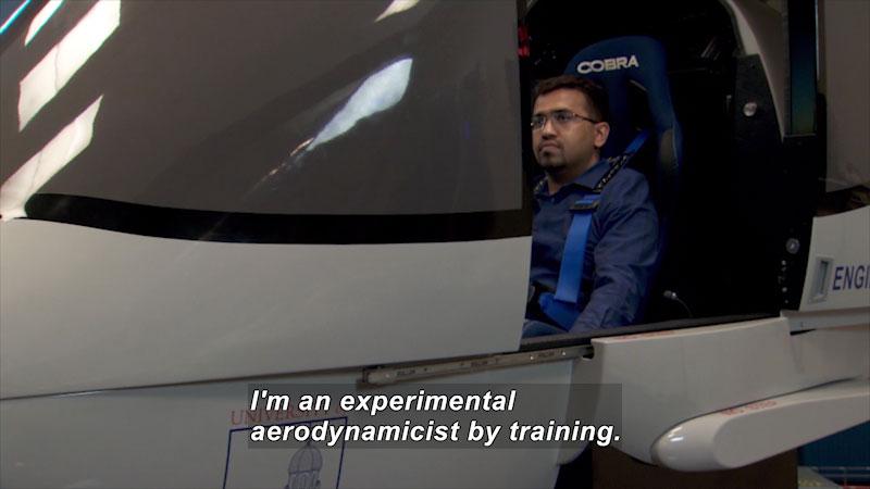 A man sitting inside a machine. Caption: I'm an experimental aerodynamicist by training.