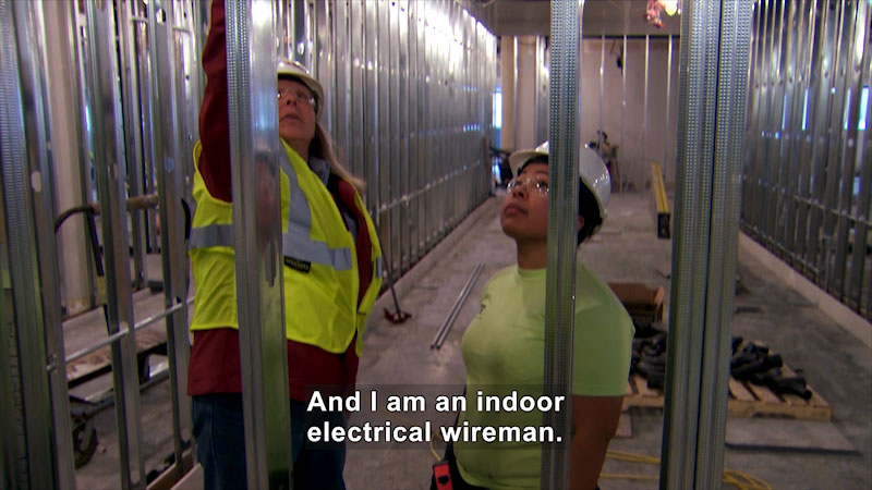 Two technicians inspecting an installation. Caption: And I am an indoor electrical wireman.