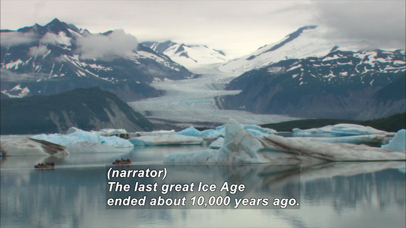 A glacier between two mountains covered in snow. Caption: (narrator) The last great Ice Age ended about 10,000 years ago.