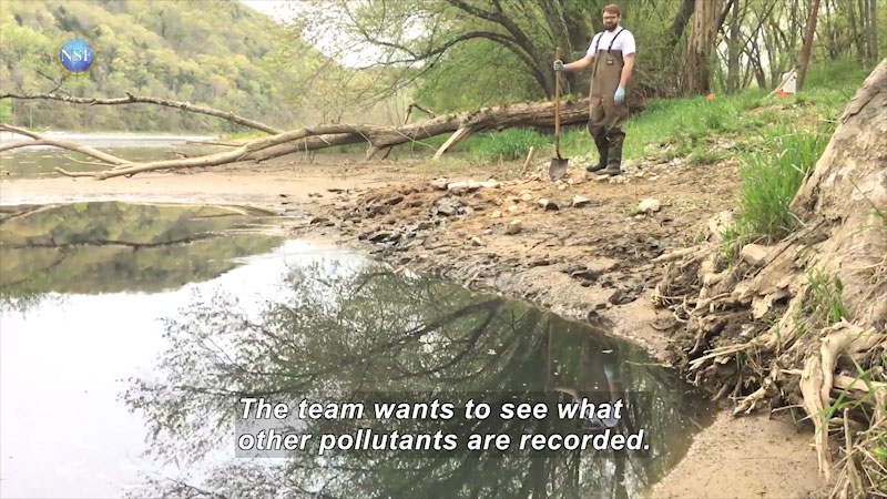 A man with a shovel standing besides a water body. Caption: The team wants to see what other pollutants are recorded.