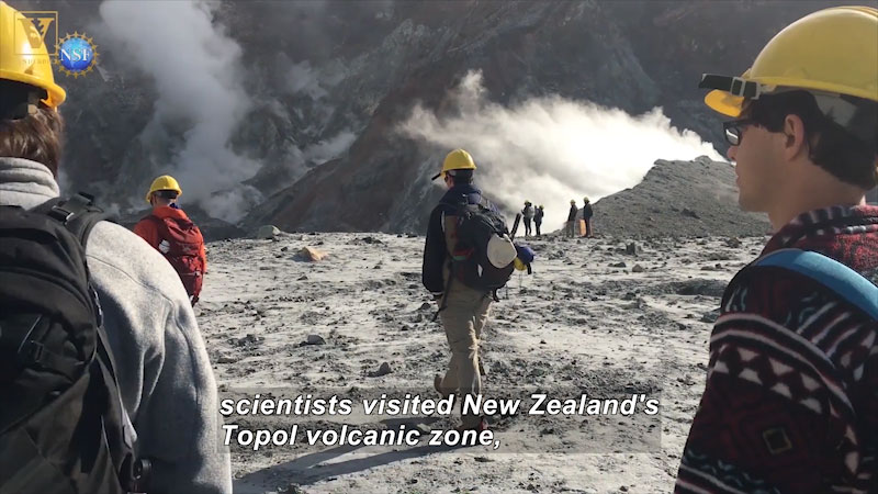 A group of people visiting an active volcano. Caption: scientists visited New Zealand's topol volcanic zone,