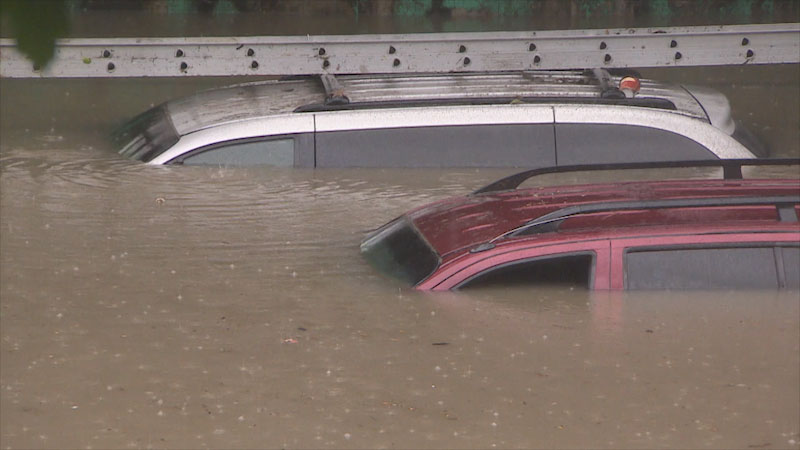 Two cars are partially submerged in flood water.
