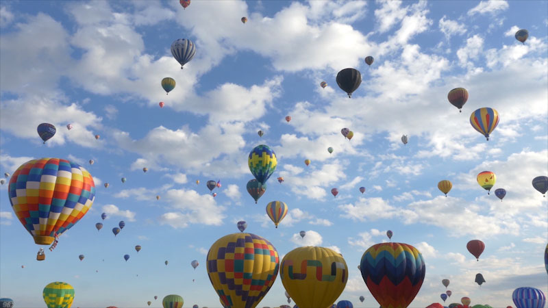 Many hot air balloons taking off into the sky.