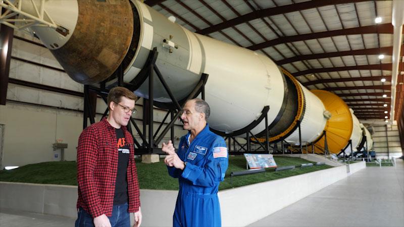 An astronaut Don Pettit talks to host Joe Hanson. A rocket is seen in the background.