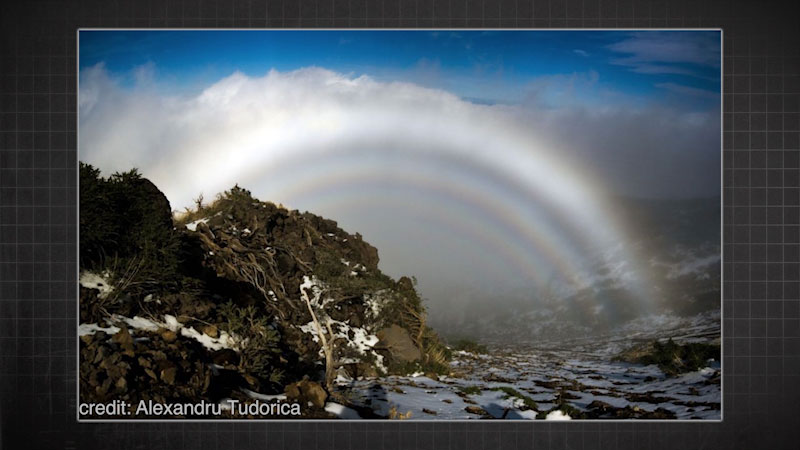 A rainbow is forms above a valley. A white band colored band is a part of the rainbow.