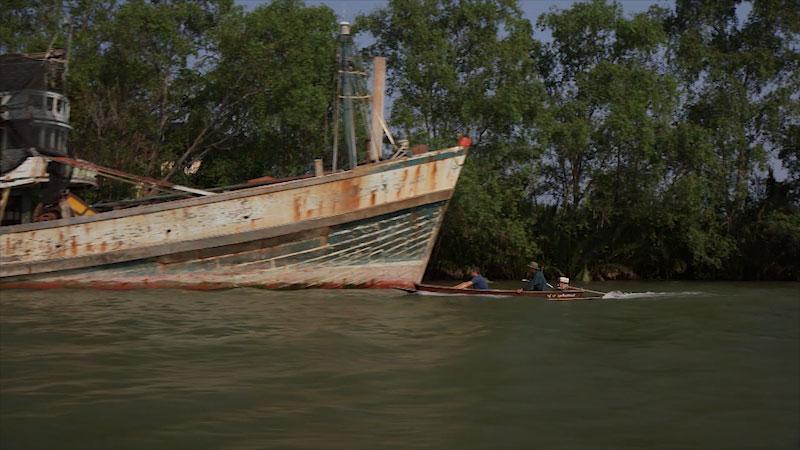 Two person on a small motor boat move toward a bigger ship.