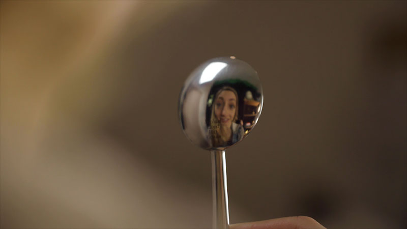 A reflection of a girl is seen on a spoon.