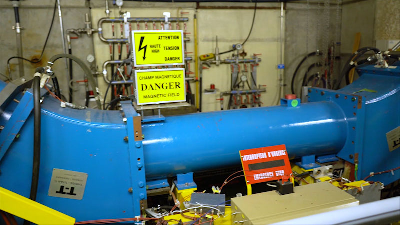 A part of the Large Hadron Collider in C E R N. Notice boards for danger and magnetic field is placed.