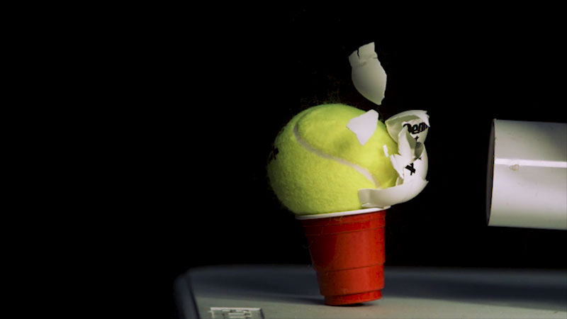 Object being shot from a tube and smashing against a tennis ball that is sitting in a plastic cup.