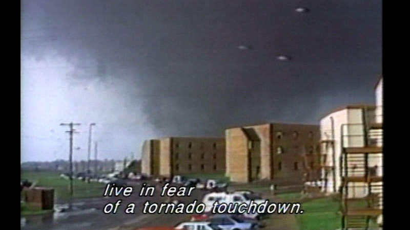Tornado approaching several buildings. Caption: live in fear of a tornado touchdown.