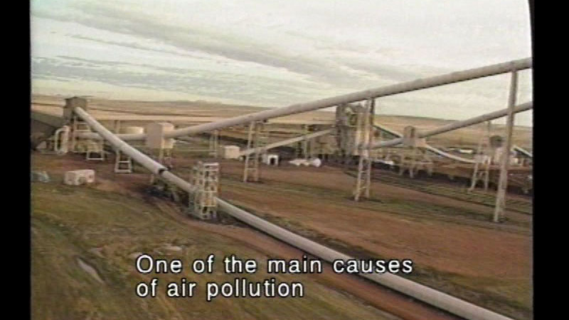 Crisscrossing industrial piping in an otherwise empty landscape. Caption: One of the main causes of air pollution