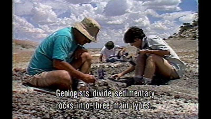 Three people sitting on ground looking at rocks. Caption: Geologists divide sedimentary rocks into three main types…