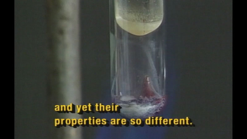 A large beaker with a substance in the bottom, a smaller beaker suspended above it. Caption: and yet their properties are so different.