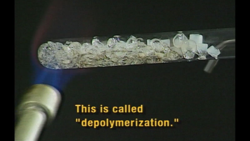 """Clear pebble substance in a test tube melting as it is being heated by a flame. Caption: This is called """"depolymerization."""""""
