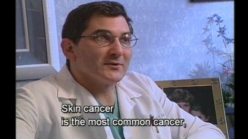 Person in a white coat talking. Caption: Skin cancer is the most common cancer,