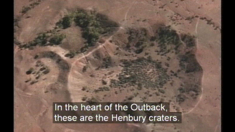 Aerial view of a large depression in the earth. Caption: In the heart of the Outback, these are the Henbury craters.
