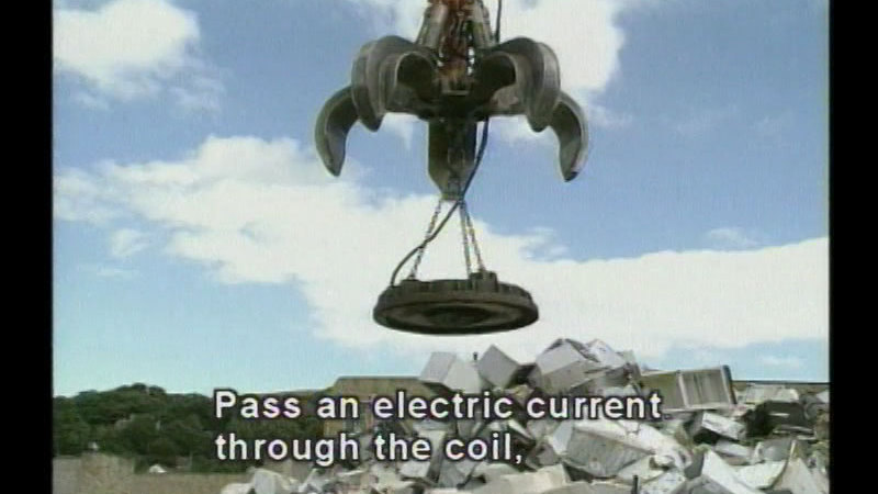 Industrial claw with giant magnet descending on a pile of trash. Caption: Pass an electric current through the coil,