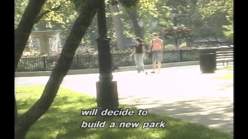 Two people walking on a paved path through a park. Caption: will decide to build a new park