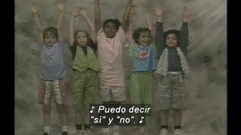 Group of children with arms raised. Spanish captions.