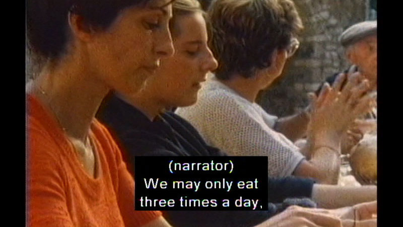People sitting at a table. Caption: (narrator) We may only eat three times a day,