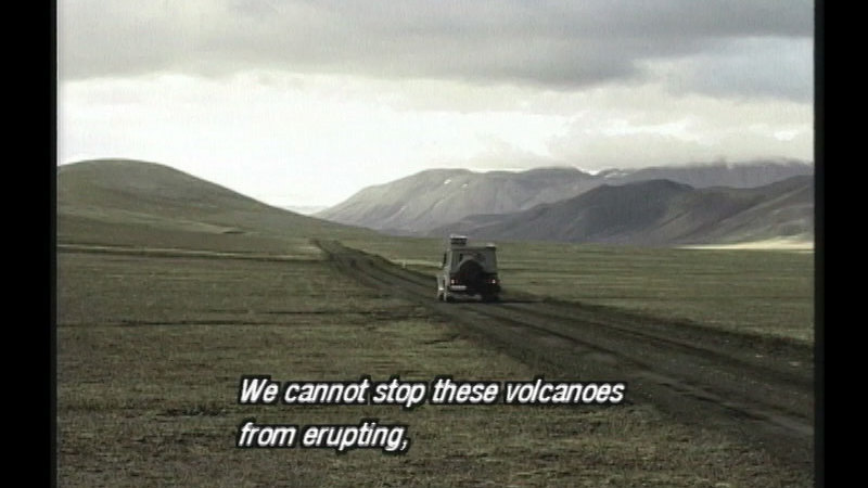 Vehicle driving along a dirt road towards mountains on a barren plain. Caption: We cannot stop these volcanoes from erupting,