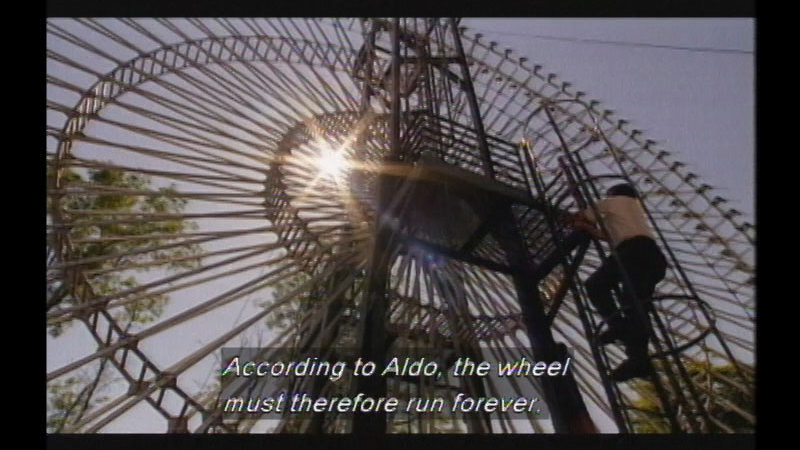 A giant stationary hollow wheel constructed of metal spokes. A person climbs up an access ladder to the center of the wheel. Caption: According to Aldo, the wheel must therefore run forever.