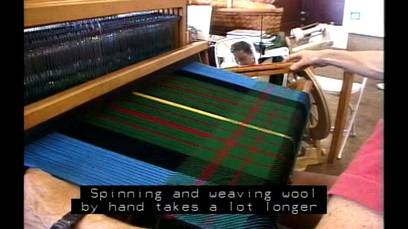 Person at a loom with a partially finished piece of patterned fabric. Caption: Spanning and weaving wool by hand takes a lot longer